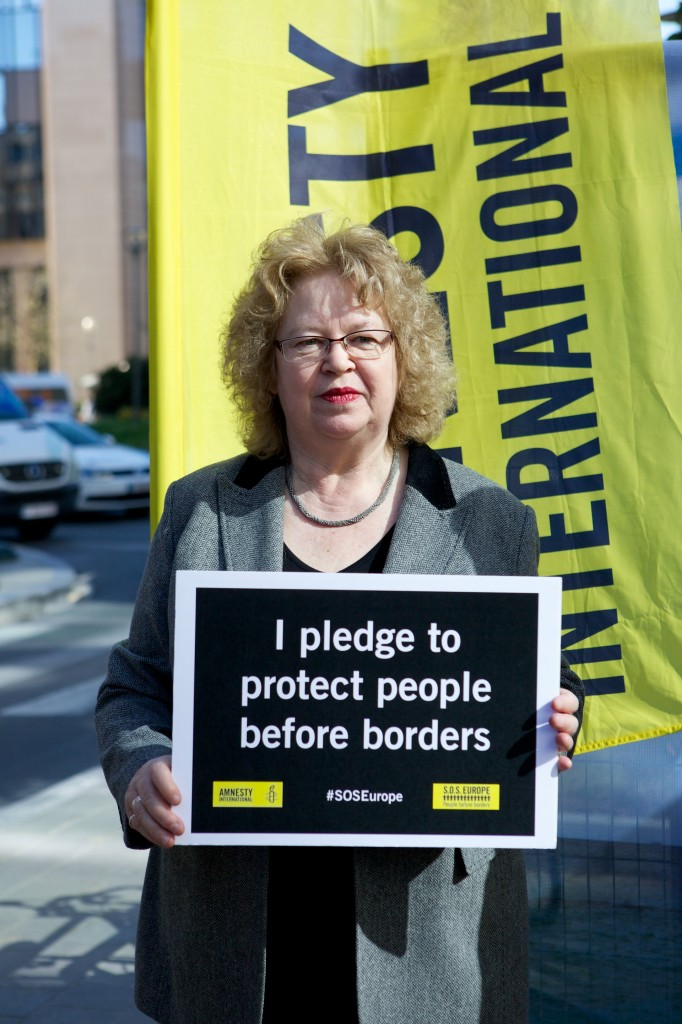 Jean holding borders action sign, pledging to protect people above borders