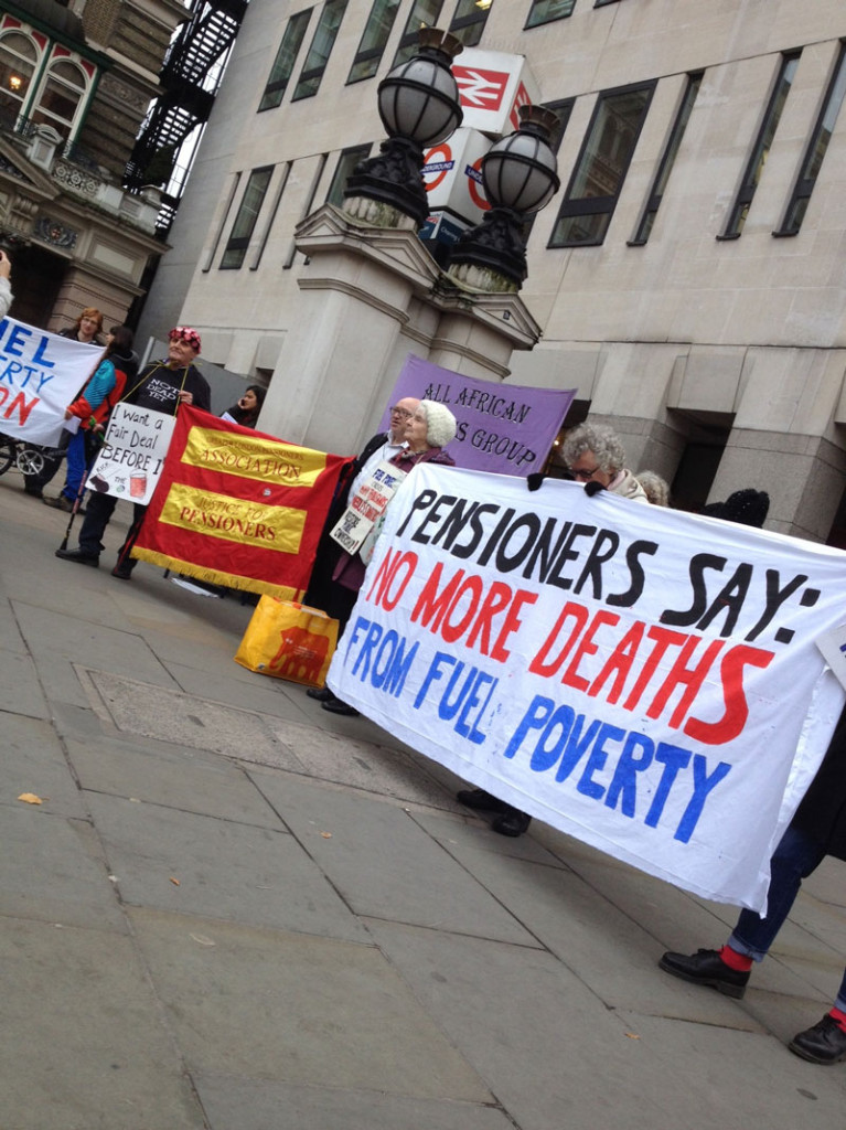 Pensioners holding banners in London against fuel poverty