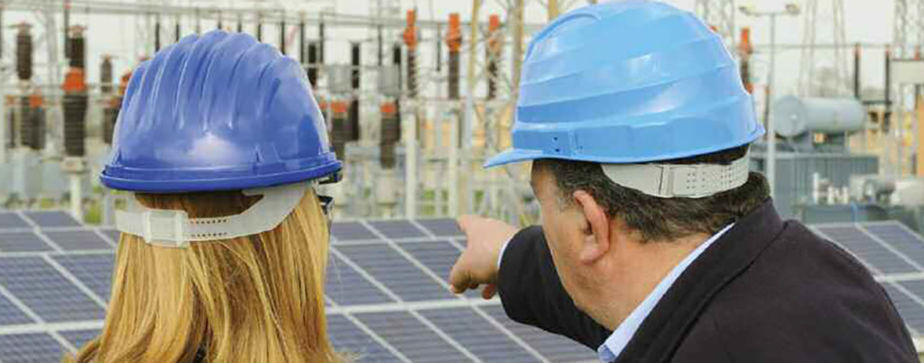 Two people point to solar panels in a construction site