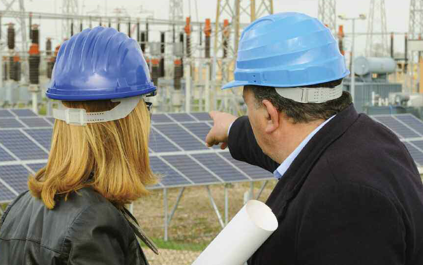 two people in hard hats on a building site pointing to solar panels