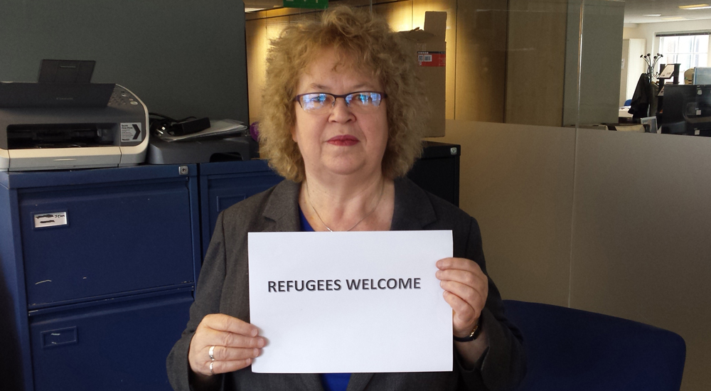 jean holding refugees welcome sign